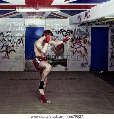 An urban street fighter in an graffiti filled basement during a training - stock photo