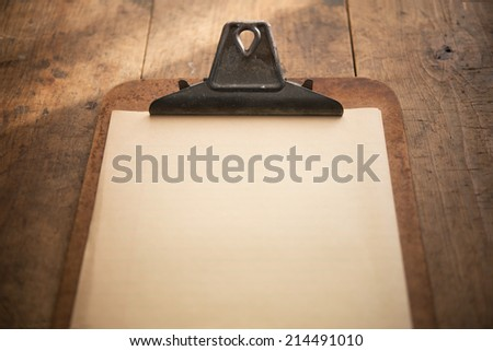 An vintage clipboard on a old wooden table, with blank old white paper.  Focus is on the writing area. - stock photo
