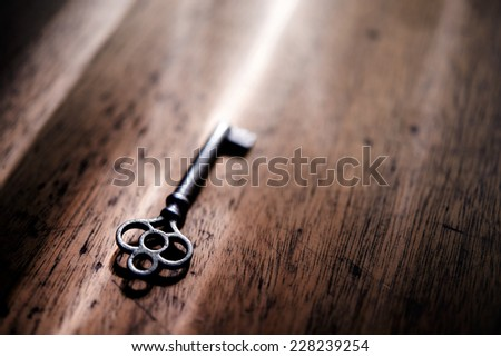 An vintage key on an grungy old desk with a beam of light coming in. - stock photo