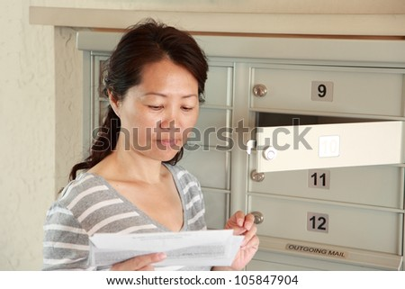 An woman opening a letter from a mailbox - stock photo