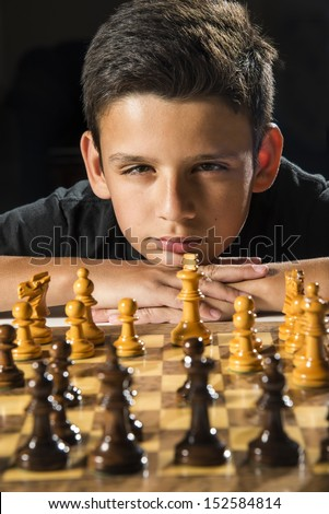 An 11 year old boy thinking about his next move during a chess game.