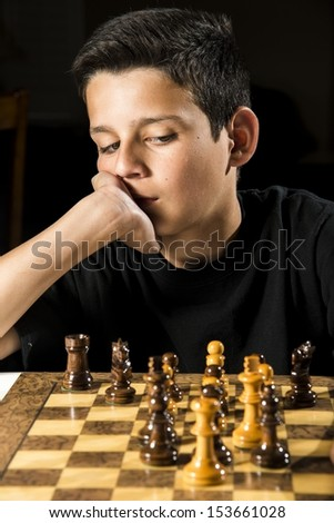 An 11 year old boy thinks about his next move during a chess game.