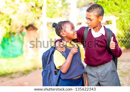 an young african brother with his arm around his younger sister showing positivity with a thumbs up while his younger sister looks up at him in adoration and pride