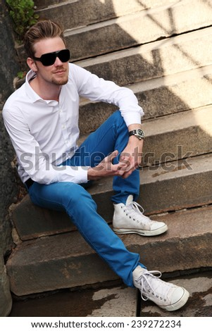 An young and attractive man in his 20s sitting down outside on a set of steps, wearing a white shirt and sunglasses. - stock photo