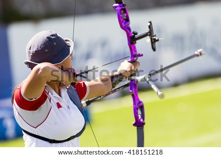 An young girl is shooting with a recurve bow during un open archery competition. - stock photo