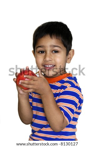 An young handsome indian kid holding an apple - stock photo