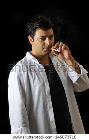 an young man smokes in studio