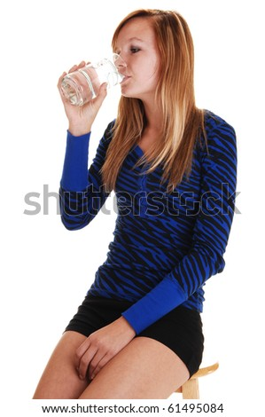 An young woman in a blue and black sweater and black shorts sitting on a chair with a glass of water in her hand, on white background.