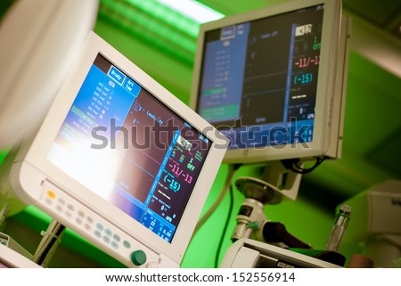 anaesthesiolog monitors in operation surgery room with green lights on - stock photo