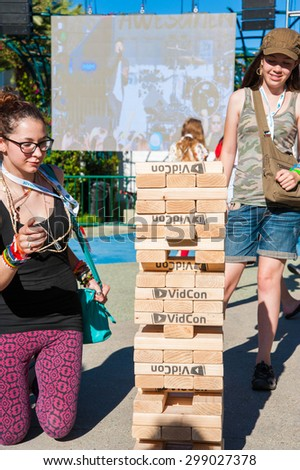 Anaheim, CA - June 22: Attendees play Jenga style game at VidCon's 6th annual conferece for YouTube creators and fans at the Anaheim Convention Center in Anaheim, California on June 22, 2015 - stock photo