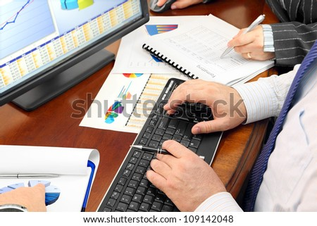 Analizing Data in the Office Hands on the Keyboard and Financial Data and Charts in the Office - stock photo