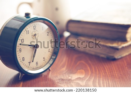 analog retro alarm clock on wooden table - stock photo