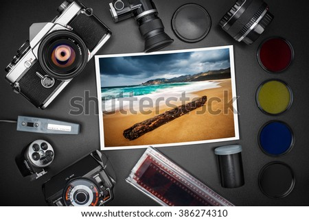 Analog SLR camera equipment around a printed photo of a beach on a stormy day - stock photo