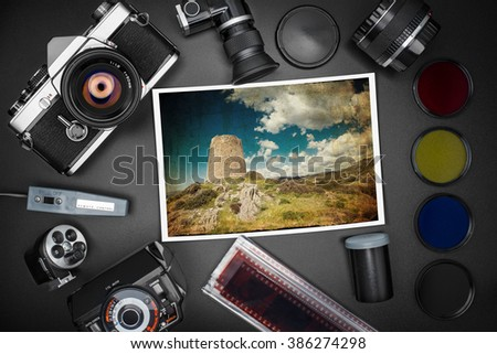 Analog SLR camera equipment around a printed photo of a Sardinian landscape with ancient Spanish wachtower in spring  - stock photo