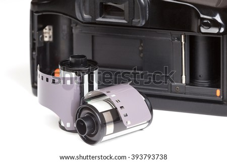 Analog SLR camera with film roll on white background - stock photo