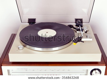 Analog Stereo Turntable Vinyl Record Player with Black Disk - stock photo