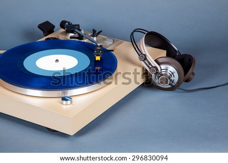 Analog Stereo Turntable Vinyl Record Player with Blue Disk and Headphones - stock photo