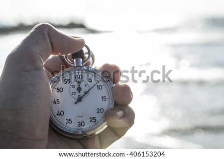 analog Stopwatch in hand with sea in the background