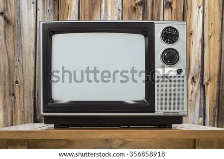 Analog television on table with rustic wod wall. - stock photo