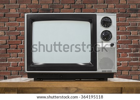 Analog television with brick wall. - stock photo