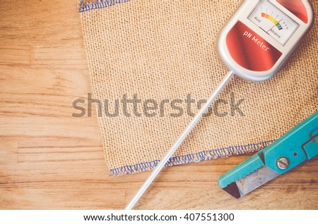 analog tool to measure soil ph and scissors on anatural wood background - copy space - stock photo