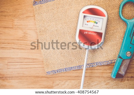 analog tool to measure soil ph and scissors on anatural wood background - copy space