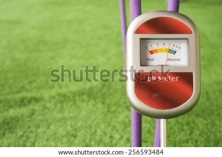 analog tool to measure soil ph on a green background - stock photo