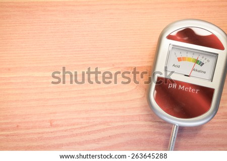 analog tool to measure soil ph on a light wood background - stock photo