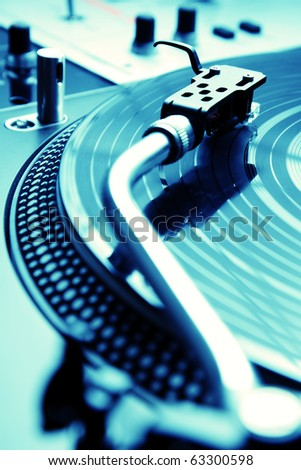Analog turntable playing record with music - stock photo