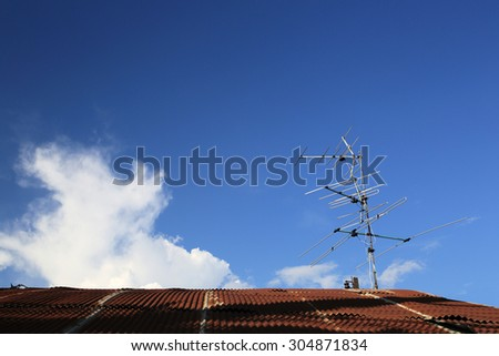 analog tv antenna on roof with blue sky background. - stock photo