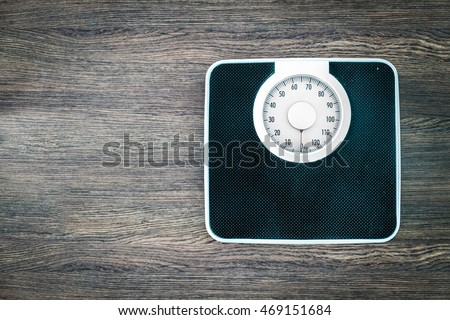 analog weight scale on wood background - text space