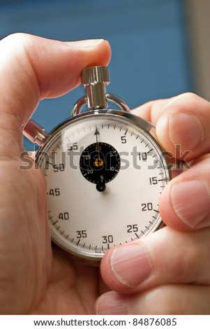 analogue stopwatch in hand