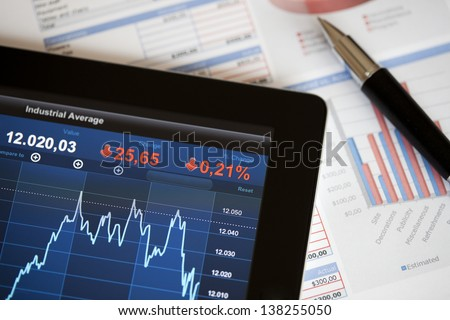 Analysing stock market with digital tablet. - stock photo