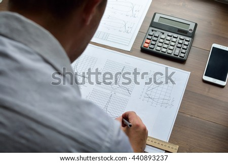 Analyst at work. Technical drawings. Paper with technical drawings and diagrams.