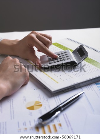 Analyzing Business Data - pen and numbers on paper - stock photo