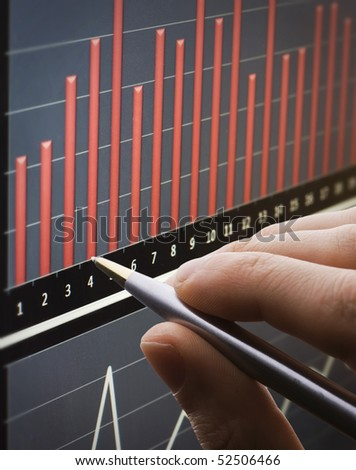 Analyzing chart on monitor - stock photo