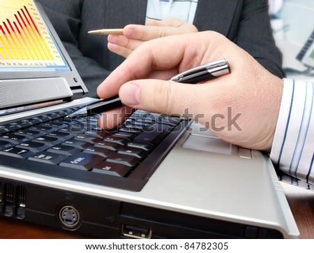 Analyzing data and charts on computer screen. - stock photo