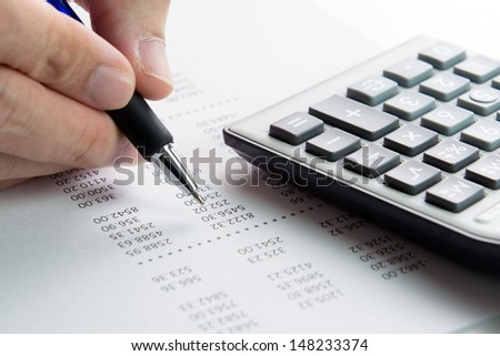 Analyzing finance report with calculator and pen - stock photo
