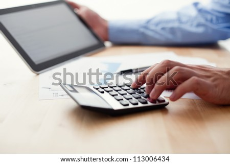 Analyzing financial data on digital tablet and counting on calculator - stock photo