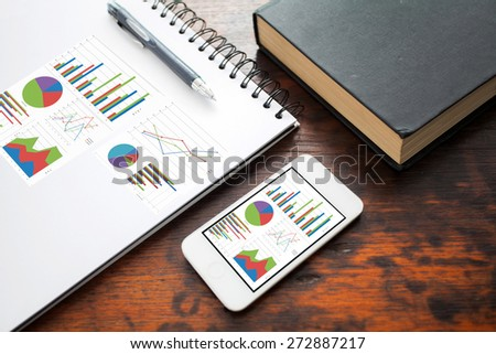 analyzing graph on smart phone with notebook on office table