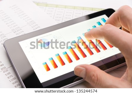 Analyzing graph with tablet-pc close-up - stock photo