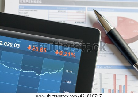 Analyzing stock market from a digital tablet over a detailed diagram with some blue prints and a pen at the background.