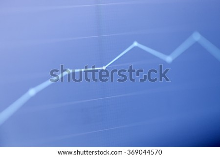 Analyzing stock market from computer screen with a detailed diagram. - stock photo
