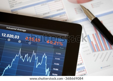 Analyzing stock market with digital tablet. Pen and some planning documents.