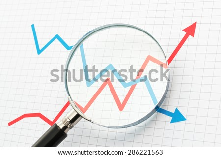 Analyzing upside growing and downside declining arrows chart with magnifying glass. Line graph and magnifying glass. Watching moves.