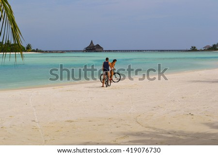 Anantara island, Maldives - November 24, 2014: the couple riding bikes along the beach at sunset