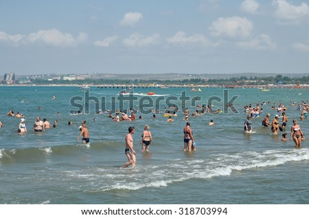 ANAPA, RUSSIA - AUGUST 16, 2015: Unidentified people swimming and sunbathing at the beach in Anapa. Anapa is a resort on the Black Sea Coast, Russia - stock photo