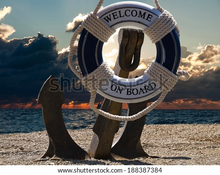 anchor in sunset with the boats on a sea and safe belt with welcome sign - stock photo