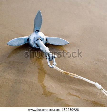 Anchor yacht with rope on beach - stock photo