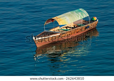 Anchored wooden boat with reflection in water, Zanzibar island - stock photo